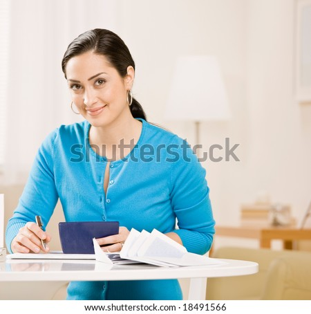Woman writing check from checkbook to pay monthly bills - stock photo