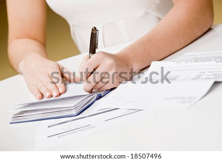 Woman writing checks from checkbook to pay monthly bills - stock photo