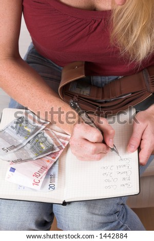 Woman writing down her expenses paid in her house hold administration book