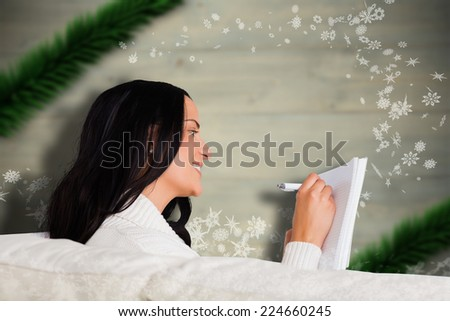 Woman writing down some notes against blurred fir tree branches - stock photo