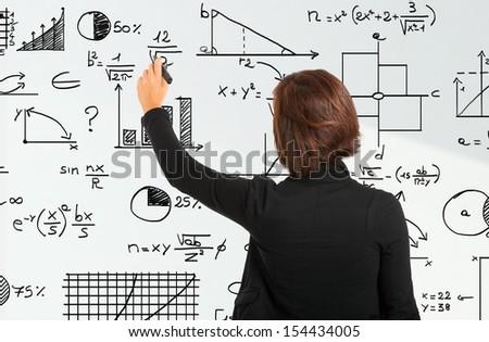 Woman writing formulas on a white board - stock photo