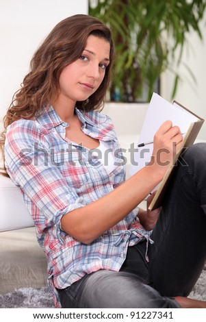 Woman writing in a book - stock photo