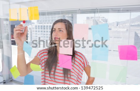 Woman writing in creative office - stock photo