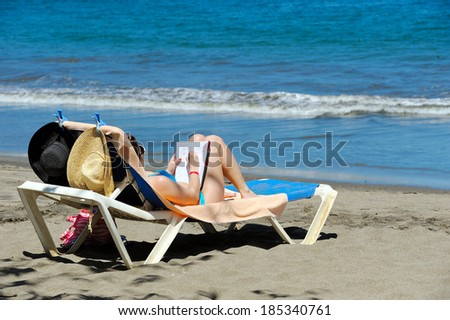Woman writing in her diary at a beach - stock photo