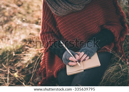 Woman writing in the notebook - stock photo
