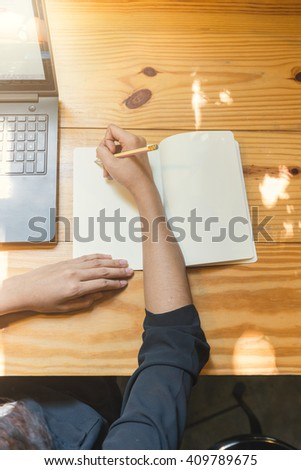 woman writing notes in her diary. Businesswoman sitting at her desk and taking notes. - stock photo