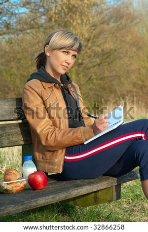 Woman writing on a bench in a park. - stock photo