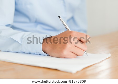 Woman writing on a sheet of paper while sitting at the office - stock photo