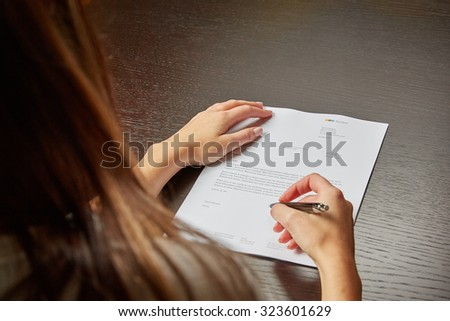 Woman writing on a white sheet of paper, signing a contract