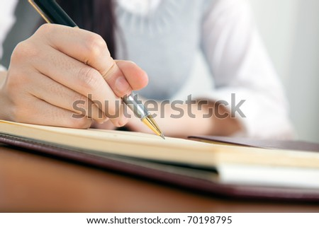 Woman writing on her agenda - stock photo