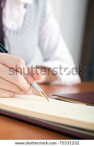 Woman writing on her agenda