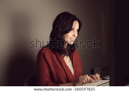 Woman writing on online chat at night