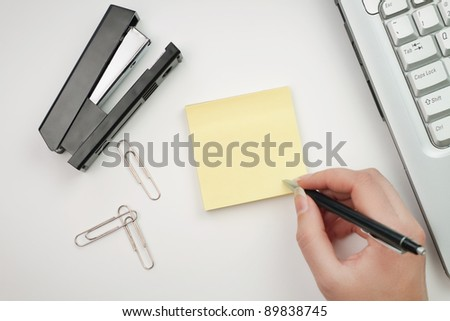 woman writing on sticker in the office - stock photo