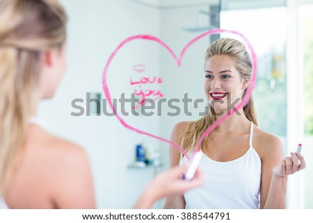 Woman writing on the mirror with lipstick in the bathroom - stock photo
