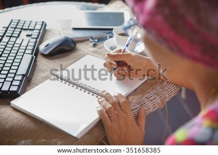 woman writing short memories note on white paper with relaxing time and emotion - stock photo