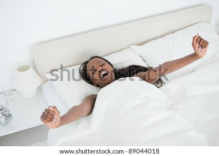 Woman yawning and stretching her arms while waking up in her bedroom - stock photo