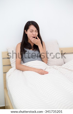 Woman yawning in bed, after waking up - stock photo