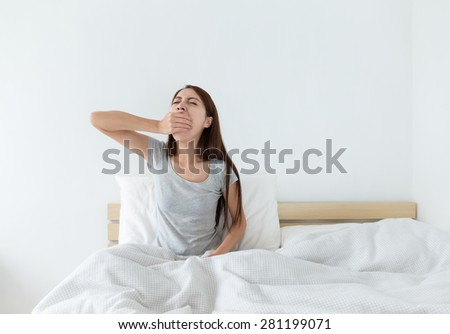 Woman yawning on the bed - stock photo