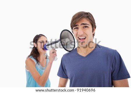 Woman yelling at her boyfriend through a megaphone against a white background - stock photo
