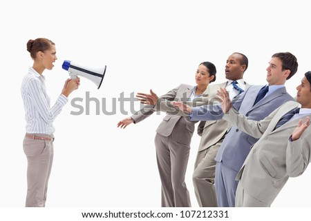 Woman yelling at people dressed in suits through a megaphone against white background - stock photo
