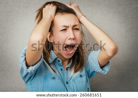 woman yells loudly angry. isolated on gray background - stock photo