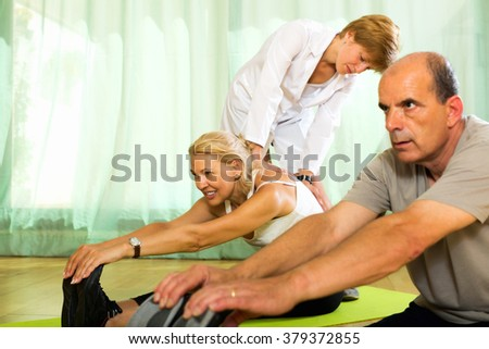 Woman yoga instructor showing new asana to smiling mature couple