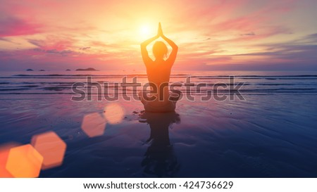 Woman yoga silhouette on the beach at amazing sunset. - stock photo