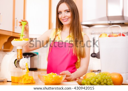 Woman young housewife in kitchen making fresh orange juice in juicer machine, preparing nutritious vitamin packed drink.  Healthy eating, vegetarian food, dieting and people concept