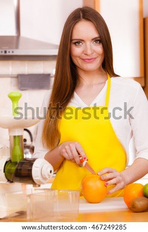 Woman young housewife in kitchen with fruits and juicer preparing to make fresh juice, cutting with knife grapefruit. Healthy eating, cooking, vegetarian food, dieting and people concept.