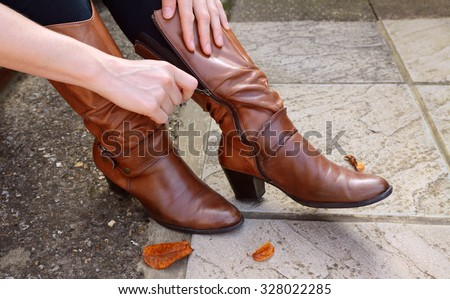 Woman zips up high-heeled tan leather boots, autumn leaves scattered at her feet - stock photo