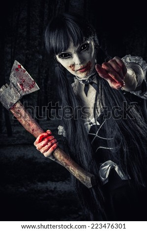 woman zombie with bloody axe extends hand to shot and pointing at you. Halloween concept. Evil ghost in night forest - stock photo