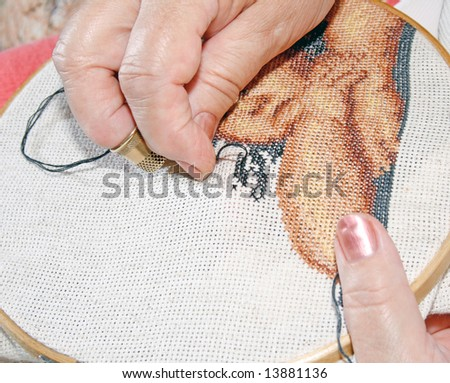 Womanish hands, executing embroidery of picture a cross, needle and varicolored threads