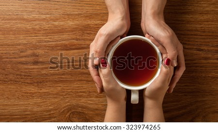 Womans and mens hands holding hot cup of tea on wooden table. Header for website - stock photo