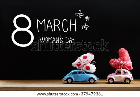 Womans Day message with pink and blue cars carrying heart cushions - stock photo