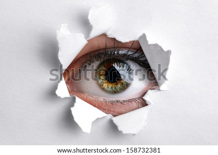 Womans eye peeking through a hole in white paper - stock photo