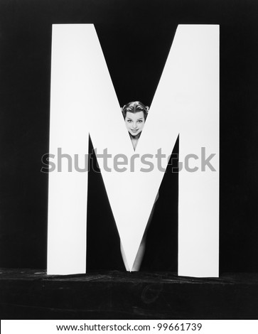 Womans face with huge letter M - stock photo