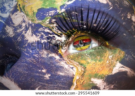 womans face with planet Earth texture and ugandan flag inside the eye. Elements of this image furnished by NASA. - stock photo