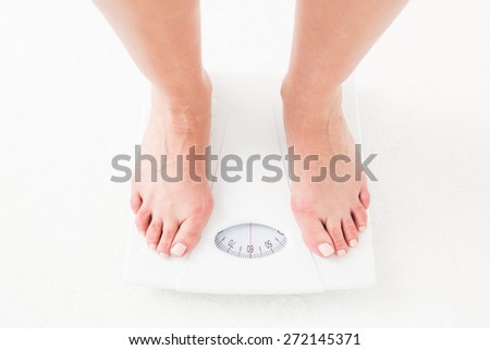 Womans feet on scales on white background - stock photo