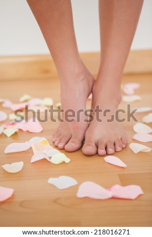 Womans feet standing around rose petals on wooden floor