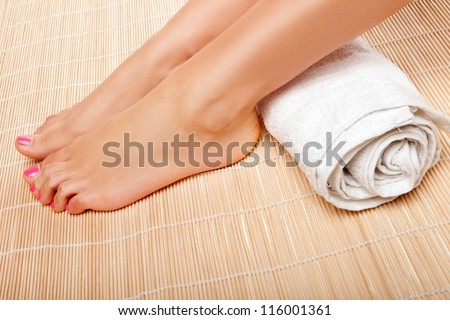 Womans feet with a rolled towel behind the ankles as she waits for a beautician to complete a beauty treatment at a spa