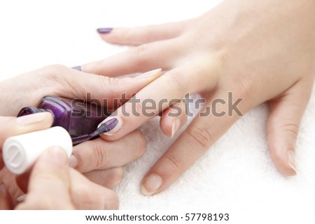 womans finger nails having purple varnish applied on white towel - stock photo