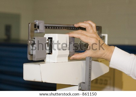 womans hand adjusts the scale - stock photo