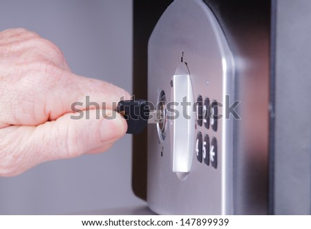 Womans hand using a key to open a safe or vault - stock photo