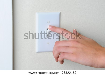 Womans hand with finger on light switch, about to turn off the lights. Closeup of hand and switch only. Horizontal format. - stock photo