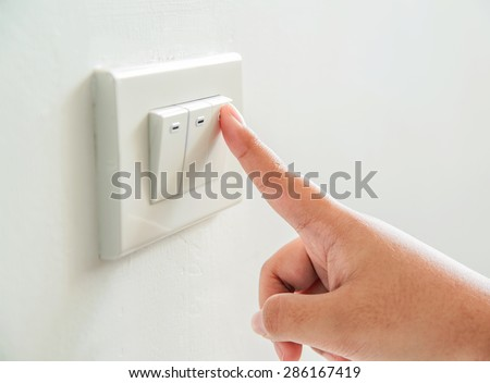Womans hand with finger on light switch to turn off the lights.