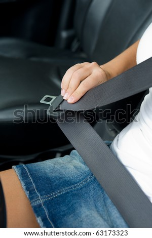 womans hand with seat belt in the car - outdoors - stock photo