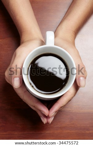 Womans hands holding a cup of coffee on a dark table - stock photo