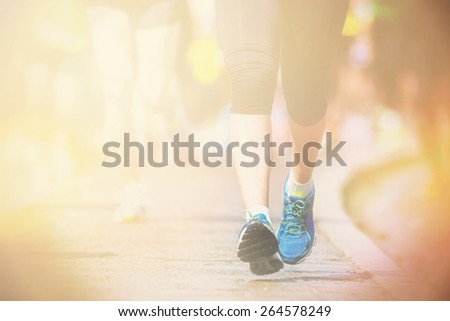 Womans leg and feet running on asphalt, closup in warm sunlight - stock photo