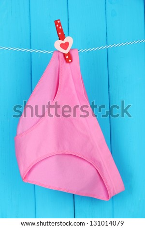 Womans panties hanging on a clothesline, on blue wooden background - stock photo