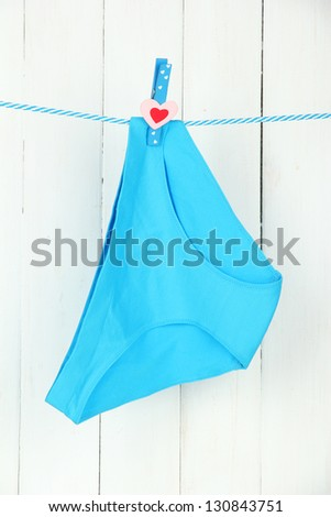Womans panties hanging on a clothesline, on white wooden background - stock photo